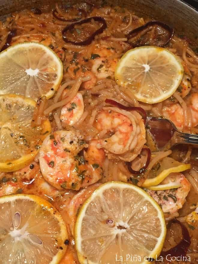 close up of fideo with shrimp using a fork to pull up shrimp