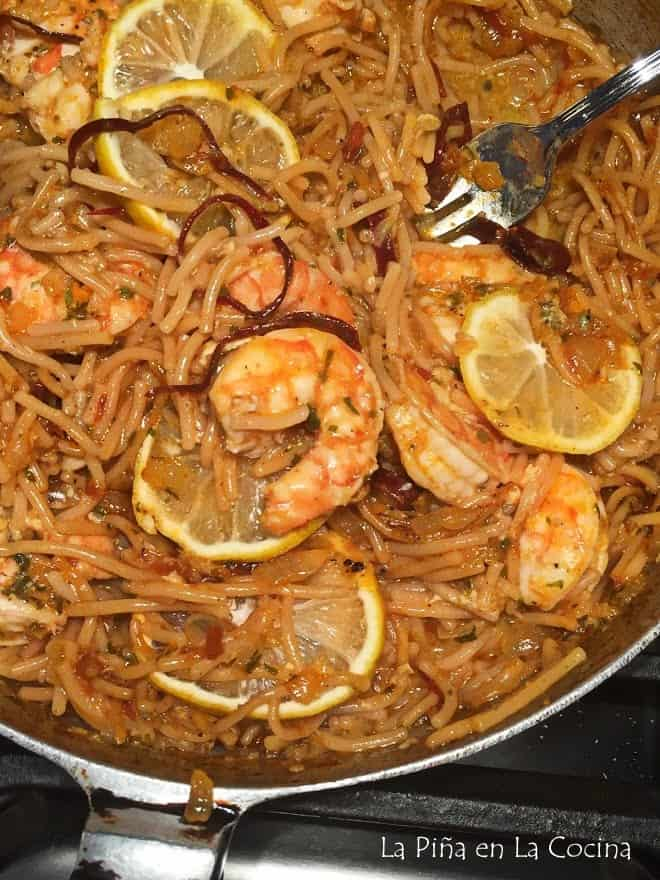 close up of fideo with shrimp in skillet, fork in fideo