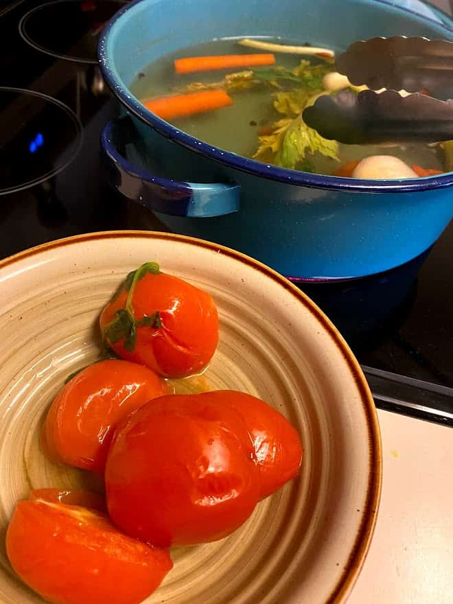removing tomatoes, onions and garlic from simmering water