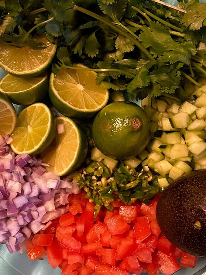 finely diced ingredients for shrimp cocktail. Tomatoes, onion, serrano, cucumbers