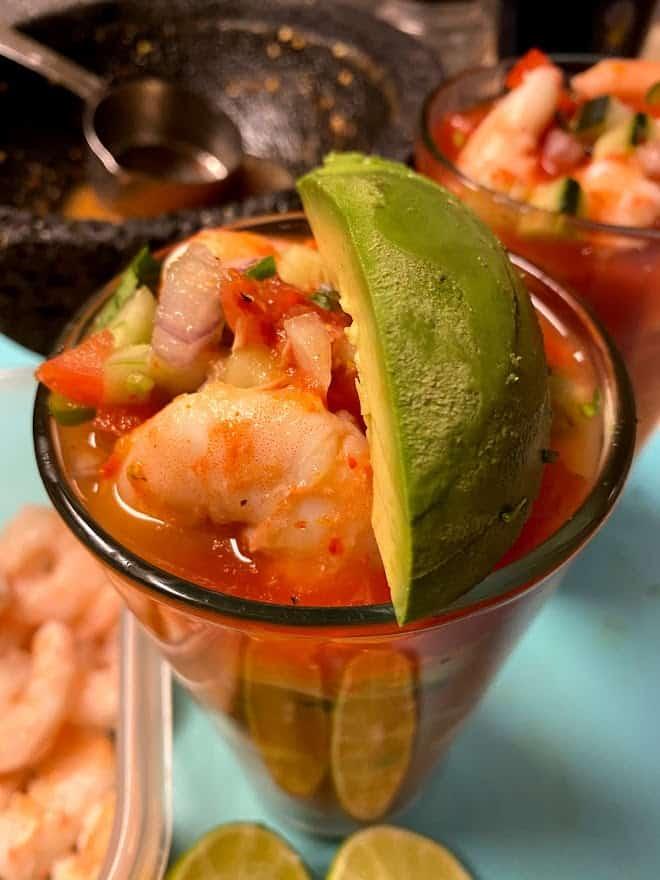 Adding avocado to the top of shrimp cocktail