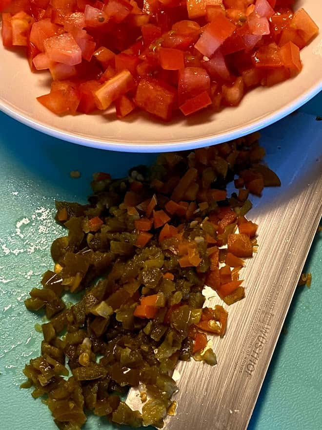 Finely chopped pickled jalapeños and carrots on cutting board