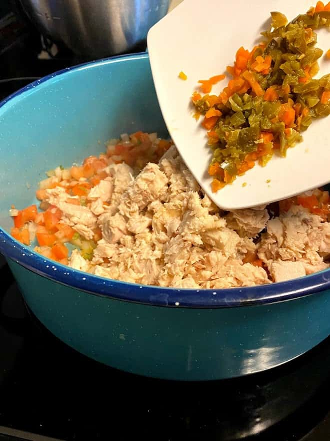 Adding pickled jalapeños and carrots to pot with tuna filling