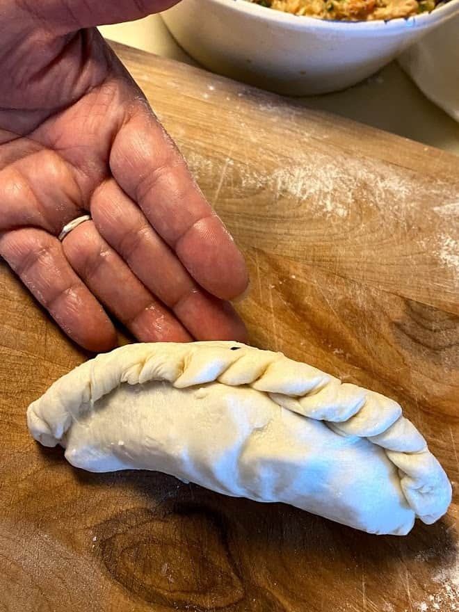 Unbaked filled empanada standing on it's side on cutting board