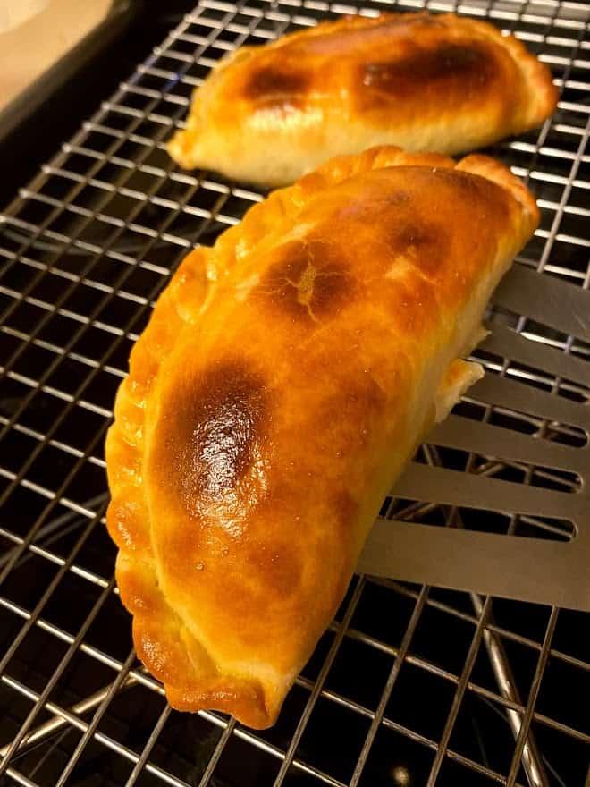 one empanada close up on cooling rack