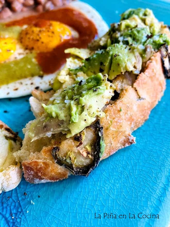 A slice of jalapeño bread with smashed avocado eggs with salsa in the back round