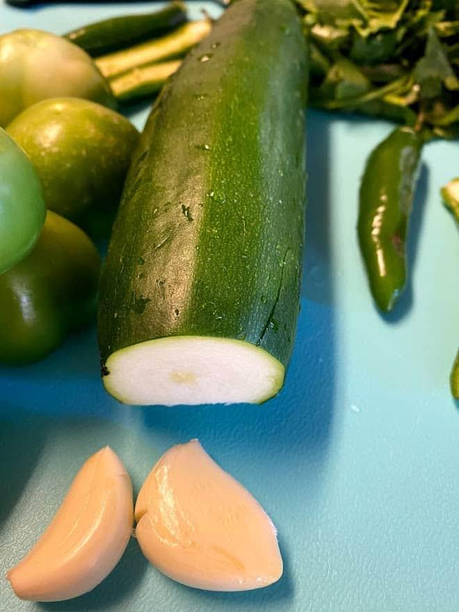 close up of fresh zucchini on cutting board with garlic