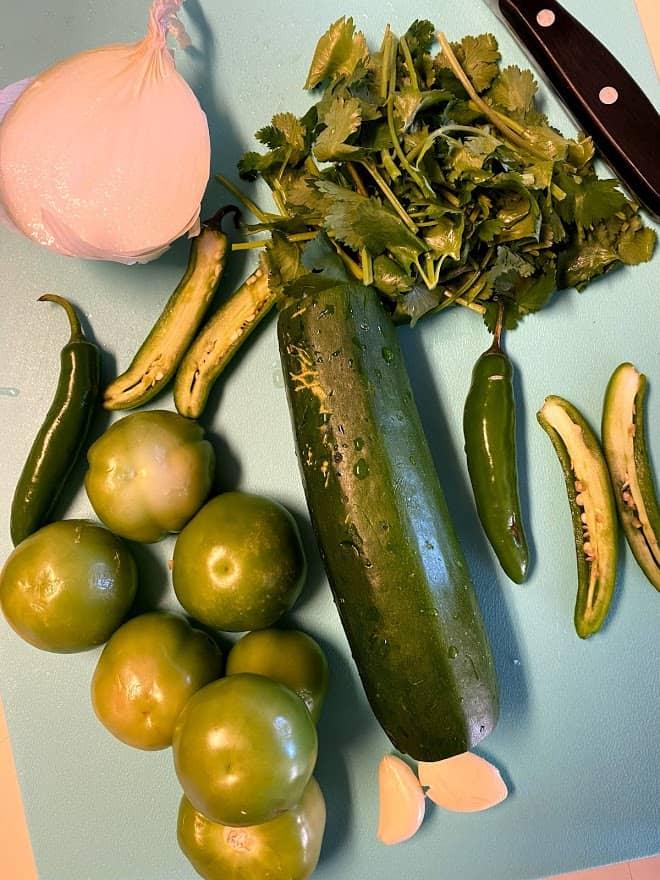 ingredients for salsa verde on cutting board. Tomatillos, serranos, garlic, onion, zucchini, onion and cilantro