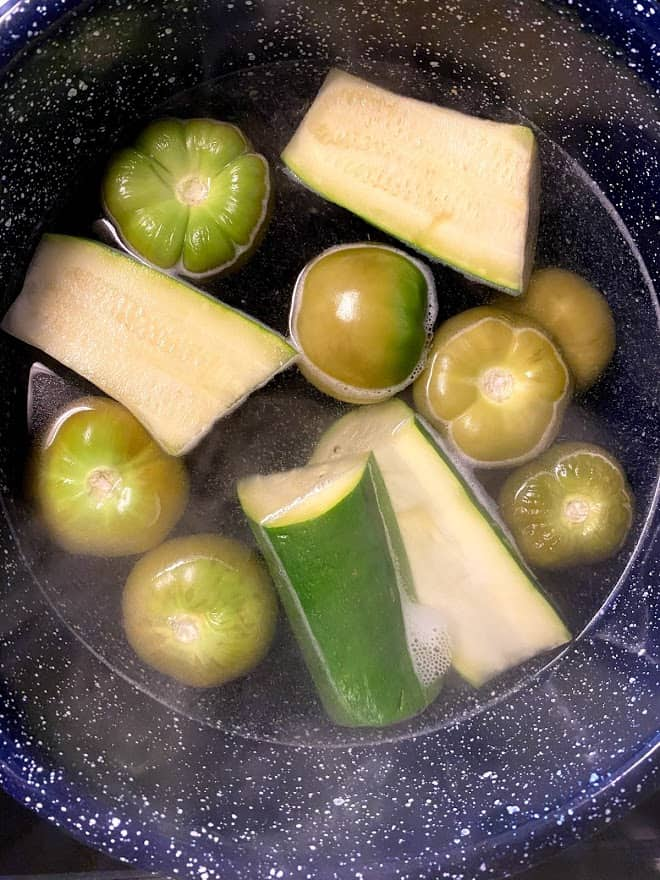 Tomatillos and zucchini simmering in water in blue pot