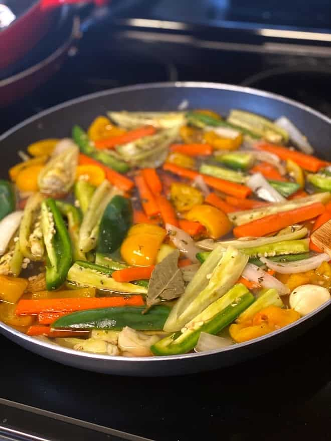 skillet on stove with hot pepper strips in vineger with herbs