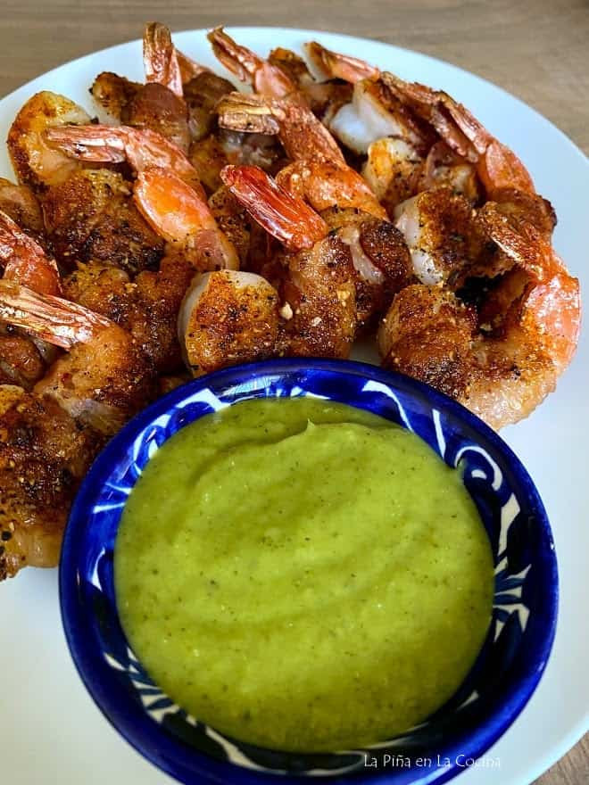 plate of bacon wrapped shrimp and small bowl of salsa verde