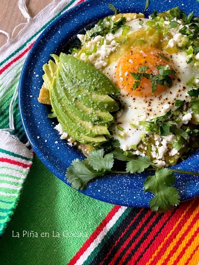 plate of green chilaquiles with sunny side up egg on top and avocado slices