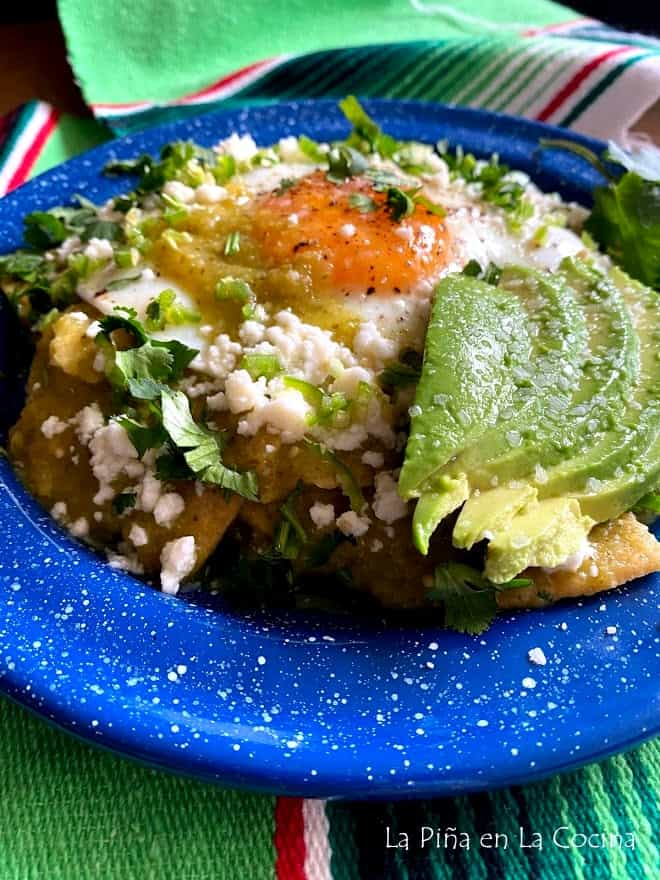 close up of green chilaquiles on blue plate