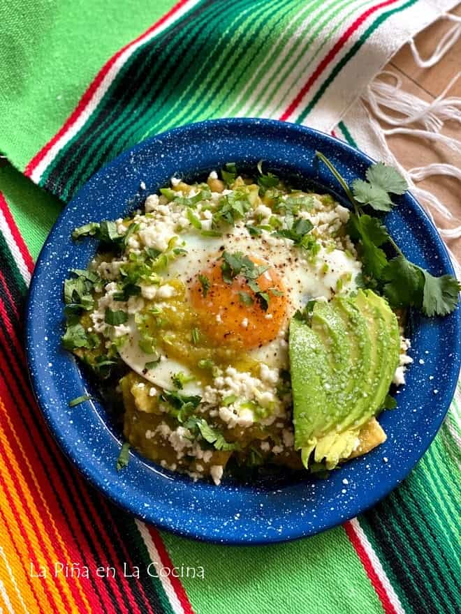 top view of a plate of green chilaquiles with sunny side egg on top