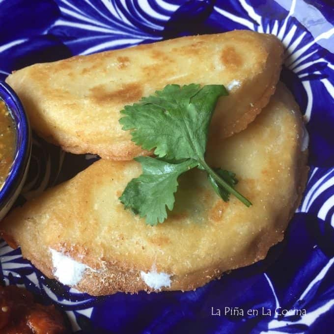 two fried quesadillas on blue and white plate with cilantro leaf
