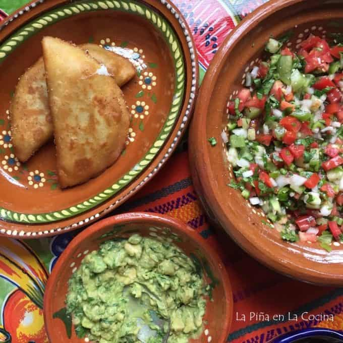 table with several plates, quesadillas, guacamole and pico de gallo salsa