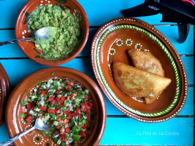 table with various plates, quesadillas, guacamole and pico de gallo salsa