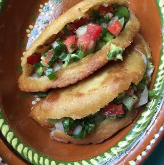 fried quesadillas sliced open and garnished with pico de gallo