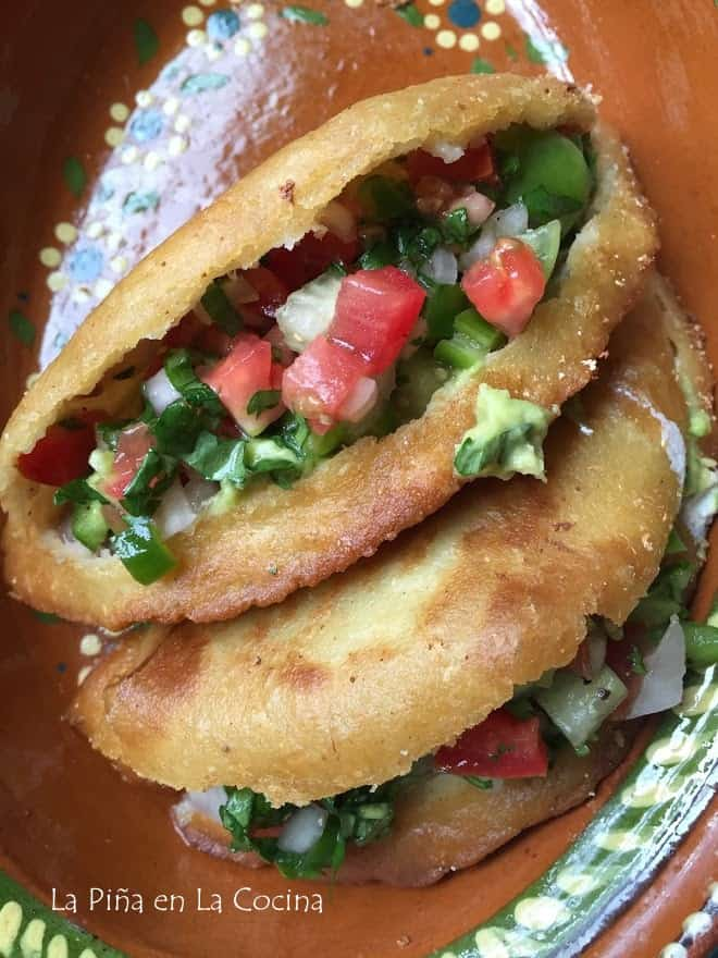 fried quesadillas sliced open and garnished with salsa