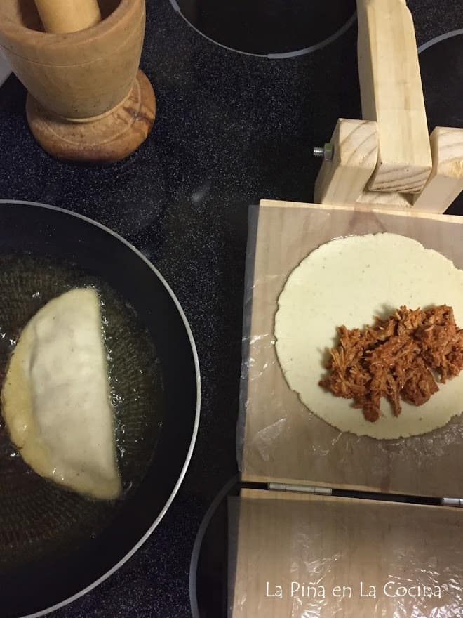 wooden tortilla press lined with plastic, pressed masa dough and meat filling on one side. Quesadilla frying in pan