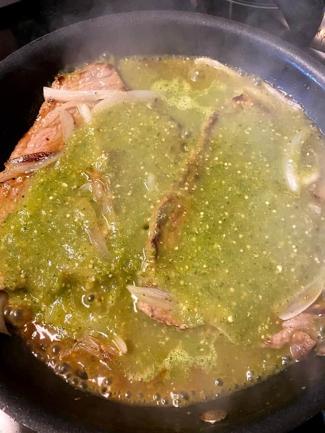 beef steak simmering in salsa verde in skillet