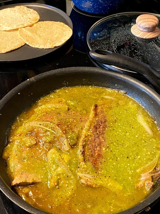 Skillet on stove top of bistec in salsa verde, tortillas on griddle cooking