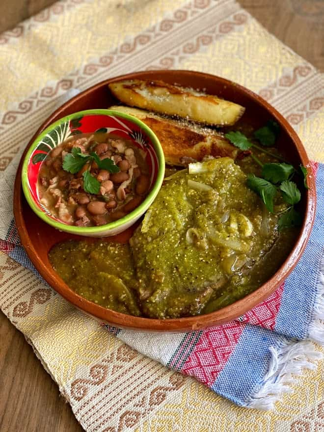plate of bistec in salsa with charro beans and potato wedges