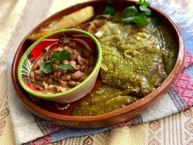 landscape image of plated bistec in salsa verde with beans and potato wedges