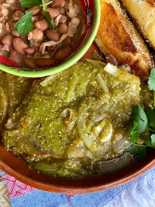 close up of bistec in salsa with beans and potato wedges