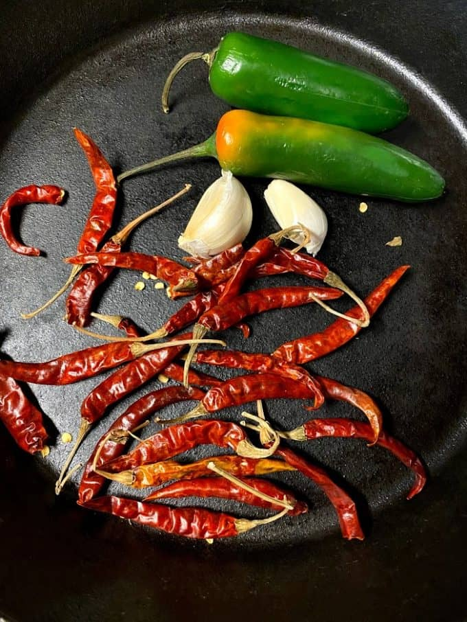 igredients for salsa on cast iron griddle, dried chile de arbol, fresh serrano peppers, garlic cloves