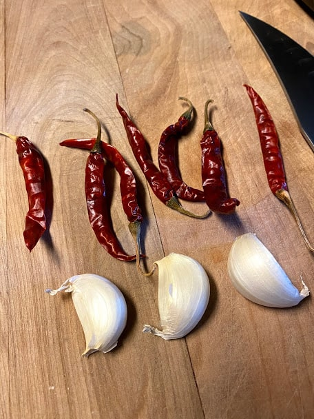 dried chile de arbol and cloves of garlic with skins on