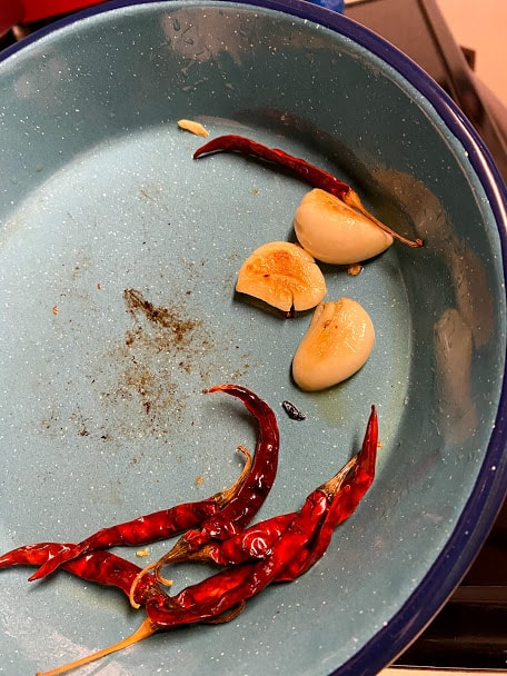 lightly fried chile de arbol and garlic in pan