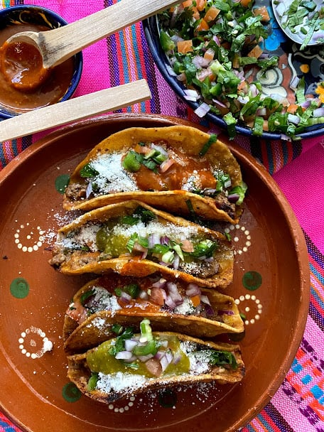 crispy beef tacos garnished with crumbled cheese and red and or green salsa