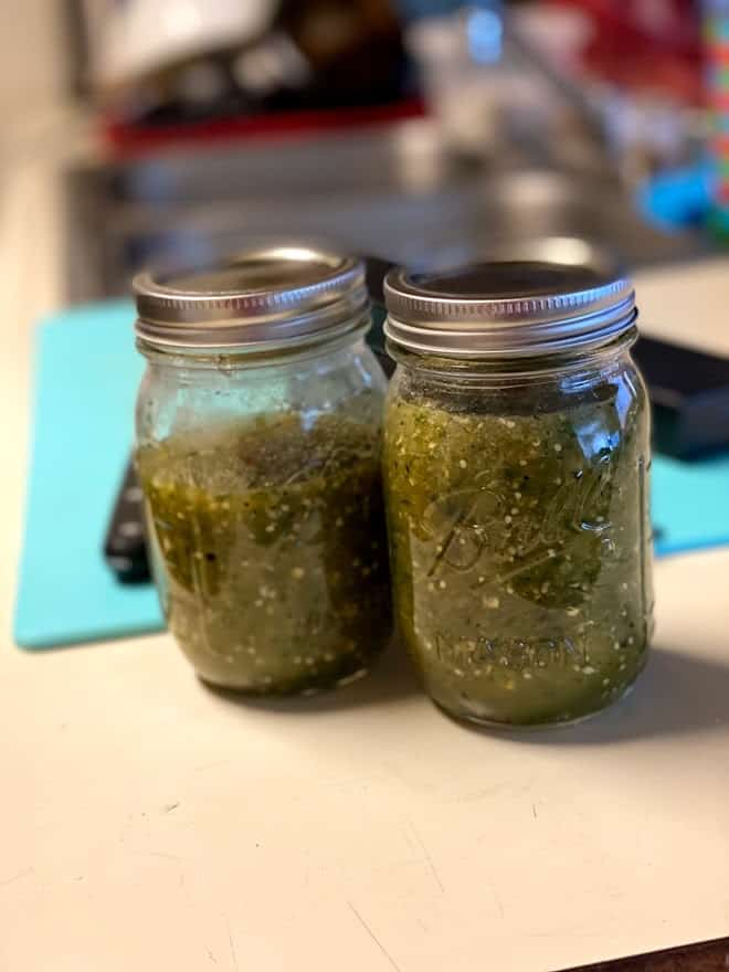 two glass mason canning jars with roasted salsa verde on kitchen counter