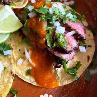 close up of flank steak tacos with spicy salsa