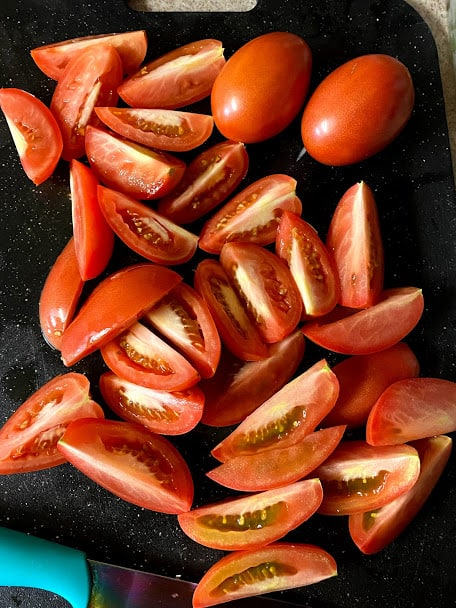 Tomatoes sliced into quarters on cutting board