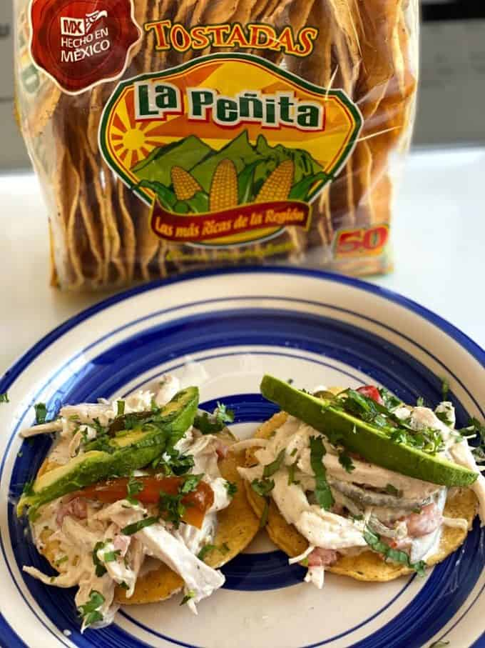 two chicken salad tostadas plated with bag of corn tostadas in the backround