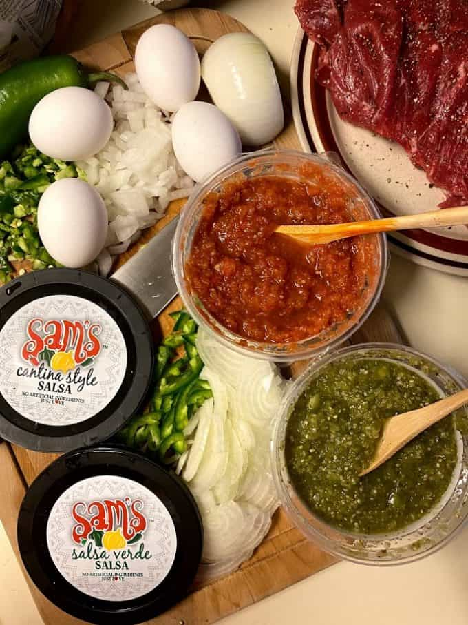 top view of both red and green salsa in containers with chopped vegetables and steak