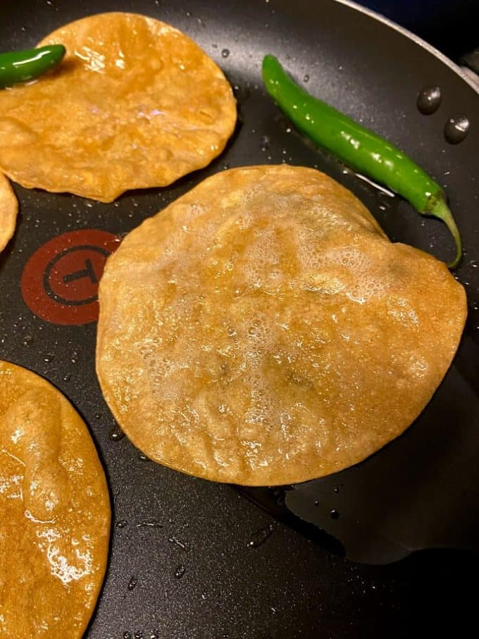 fried corn tortillas in large skillet, close up