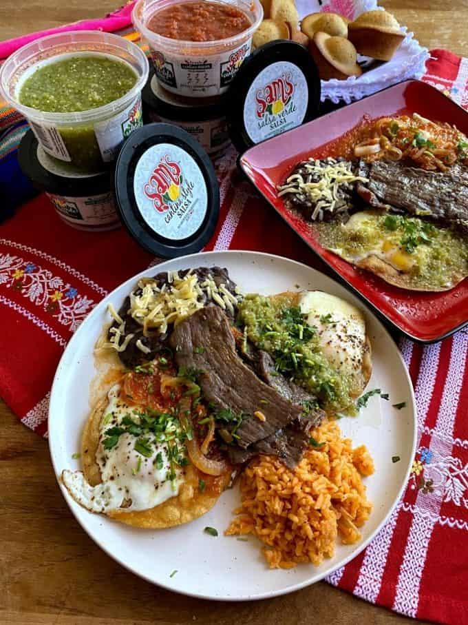 table set with two plates of huevos divorciados with sam's fresh salsa
