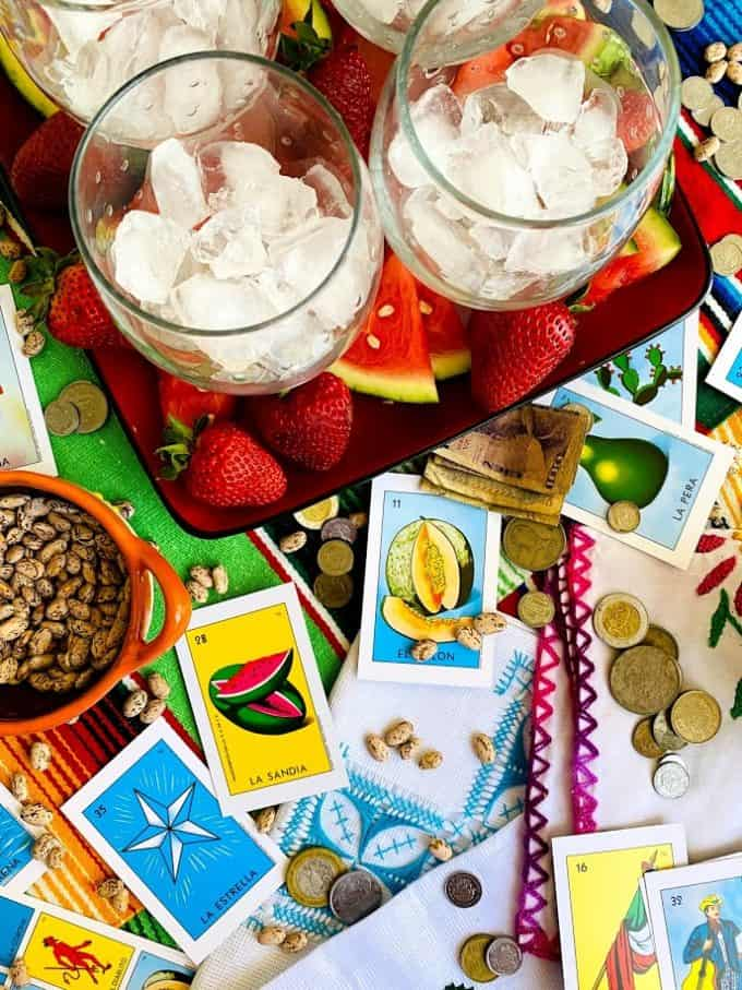 glasses for sangria filled with ice. Mexican loteria cards, money, beans on table