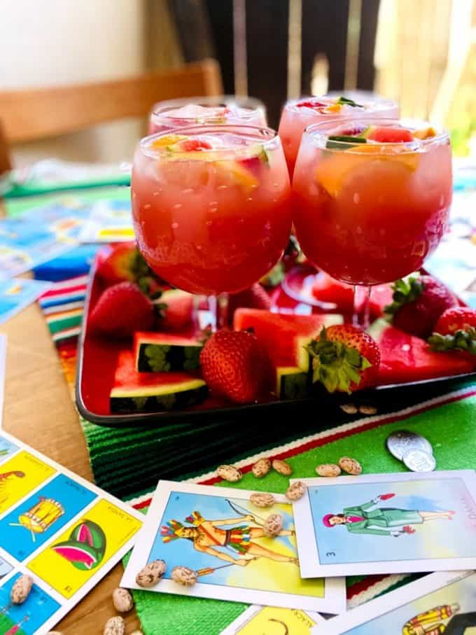 four glasses of sangria with fruit garnish. Mexican loteria cards with pinto beans and Mexican coins