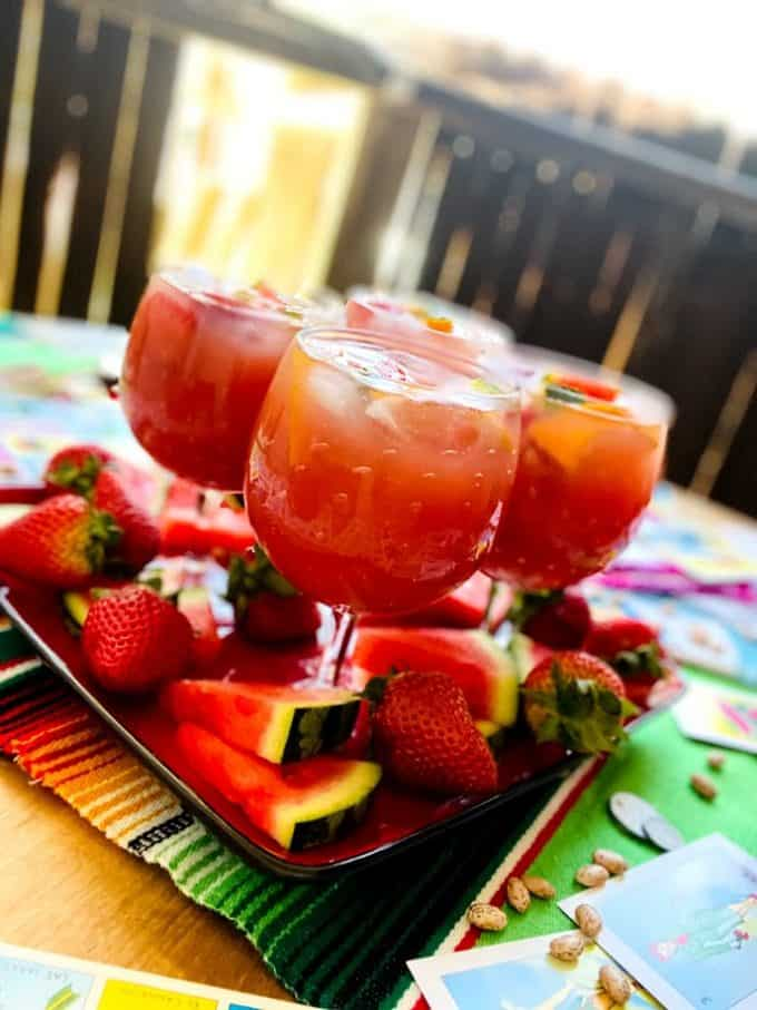 four glasses of sangria on a platter with fresh fruit