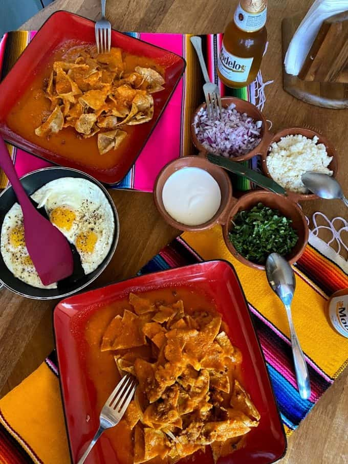 table set with two plates of chilaquiles with fresh