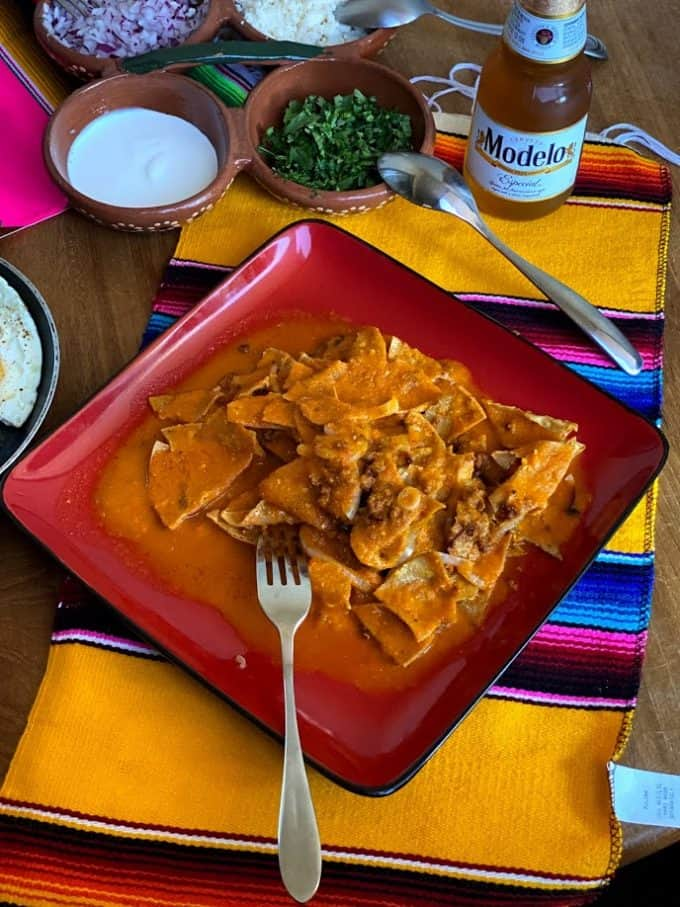big plate of chilaquiles with spicy red salsa, fresh garnishes, bottle of beer