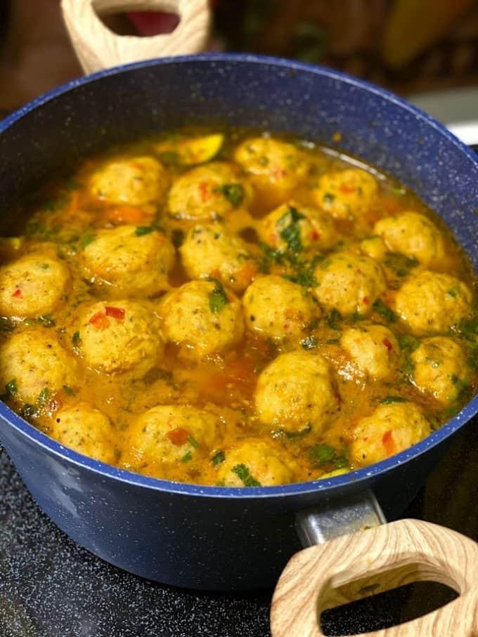 big pot of shrimp meatballs sitting on the stove top