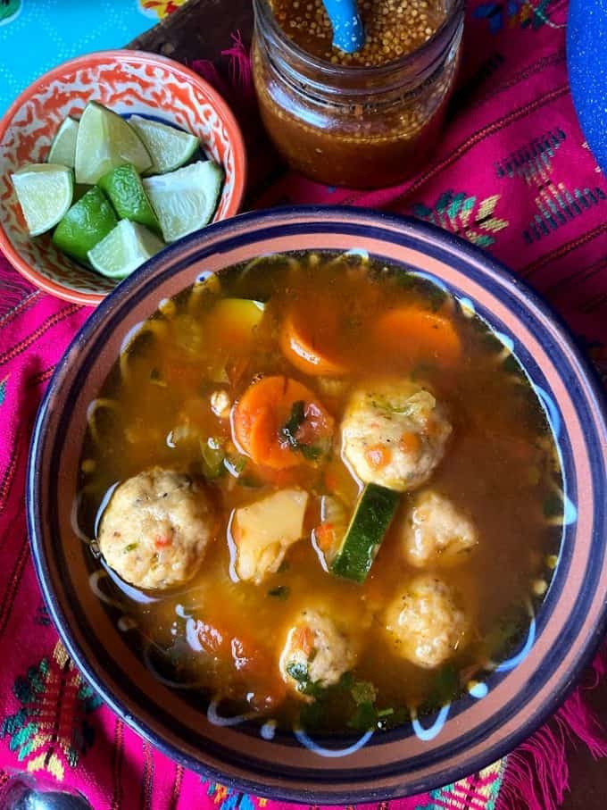 top view of bowl of shrimp meatballs in broth with vegetables