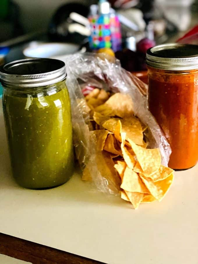 red and green salsas in mason jars with tortilla chips in the middle