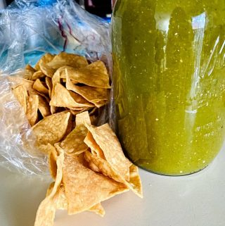 salsa verde in a tall mason jar with chips on the side