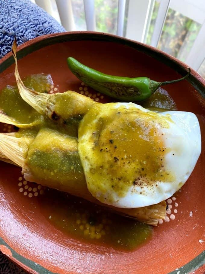 tamales with sunny side up egg and spicy salsa verde on top